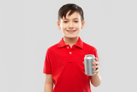boy in red t-shirt drinking soda from tin can Banco de Imagens