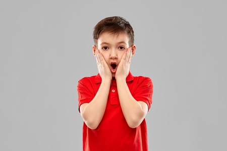 shocked little boy in red t-shirt touching face Stockfoto