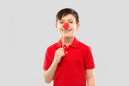 smiling boy with red clown nose party prop