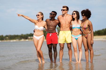 Amigos felices abrazándose en la playa de verano