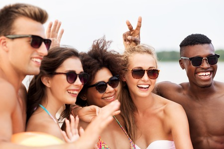 happy friends in sunglasses on summer beach