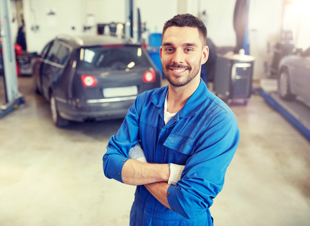 Happy auto mechanic man or smith at car workshop Stockfoto