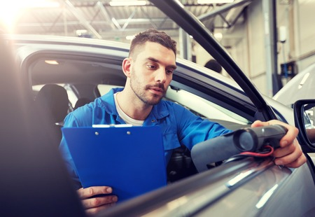 Mechanic man with diagnostic scanner at car shop 版權商用圖片 - 121996519