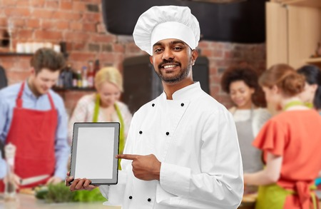 Indian chef with tablet computer at cooking class