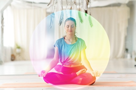 Mujer meditando en posición de loto en el estudio de yoga