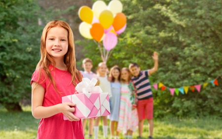 Red haired girl with gift at birthday party Banque d'images