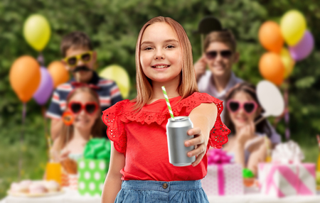 Smiling girl with can drink at birthday party Фото со стока