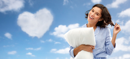 Happy young woman in pajama with pillow over sky Imagens