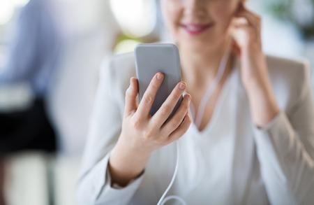 Businesswoman with earphones and smartphone 版權商用圖片