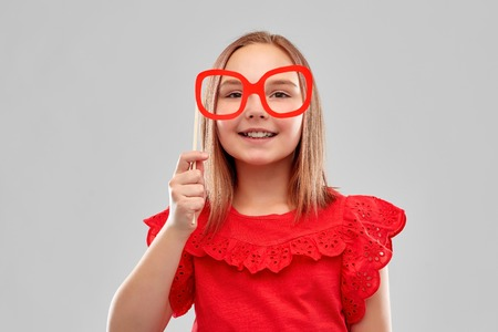 Beautiful smiling girl with big paper glasses