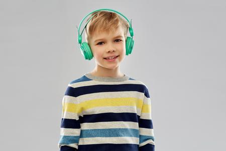 Smiling boy in headphones listening to music Фото со стока