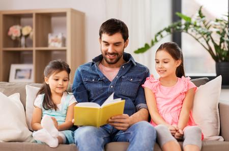Padre felice con le figlie che leggono il libro a casa Archivio Fotografico