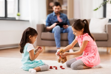 Girls playing with toy crockery and teddy at home