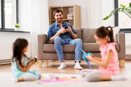 Padre con teléfono inteligente mirando a sus hijas jugando en casa