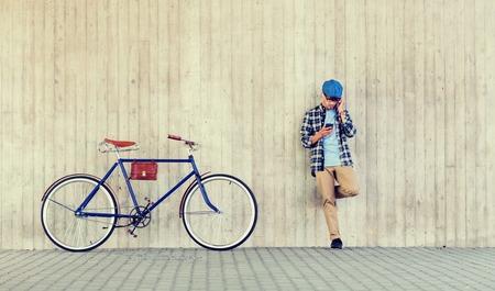 gente, estilo, tecnología, ocio y estilo de vida - hombre joven inconformista en auriculares con teléfono inteligente y bicicleta de piñón fijo escuchando música en la pared de la calle de la ciudad