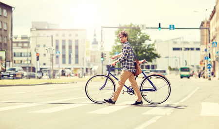 people, style, city life and lifestyle - young hipster man with shoulder bag and fixed gear bike crossing crosswalk on street Stock Photo