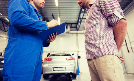 auto service, repair, maintenance and people concept - mechanic with clipboard talking to man or owner at car shop Standard-Bild - 122209027