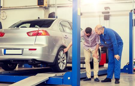 autoservice, reparatie, onderhoud en mensenconcept - monteur met klembord en man of eigenaar die wiel in autowinkel laat zien Stockfoto
