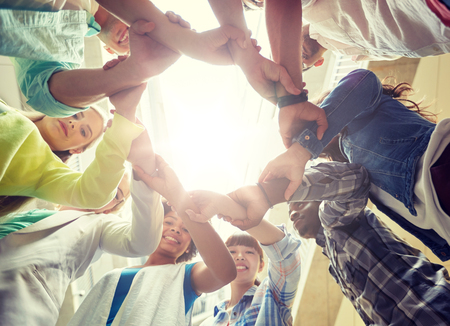 education, school, teamwork and people concept - international students making circle of hands