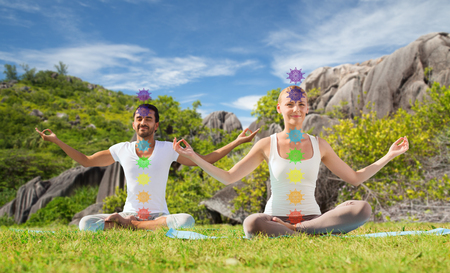 mindfulness, spirituality and outdoor yoga - couple meditating in lotus pose with seven chakra symbols over seychelles nature background