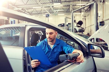 service, reparatie, onderhoud en mensenconcept - monteur met diagnostische scanner voor auto's en klembord die autosysteem controleren in werkplaats