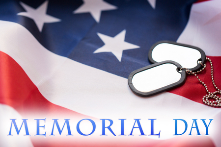 military forces, patriotism and memorial day concept - close up of american flag and badges or dog tags