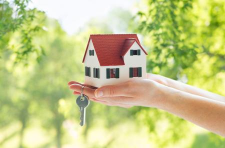 concepto de hipoteca, bienes raíces y propiedad - cerca de manos sosteniendo el modelo de la casa y las llaves de la casa sobre fondo verde natural