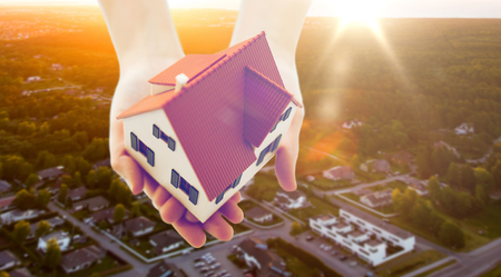 real estate, accommodation and property concept - close up of hands holding house or home model over suburbs background