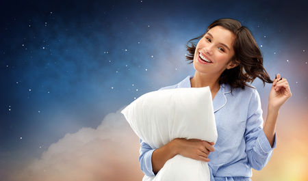 people and bedtime concept - happy young woman in pajama hugging pillow over starry night sky and cloud background Imagens