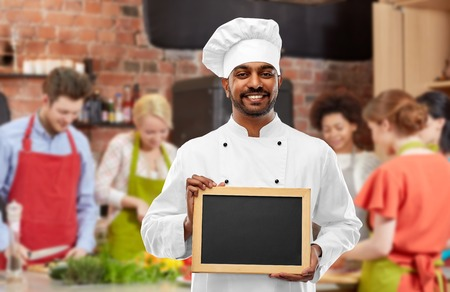cooking class, profession and people concept - happy male indian chef in toque with blank chalkboard for menu over group of students background 写真素材