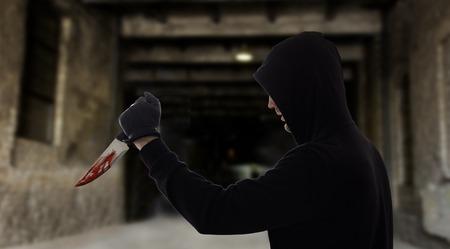 crime scene, murder and killing concept - close up of criminal or murderer with blood on knife over dark gateway background