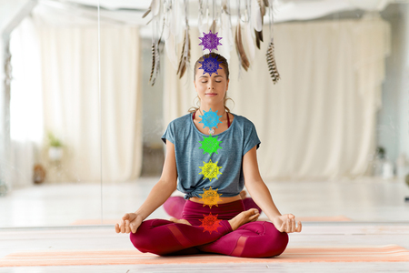 mindfulness, spirituality and healthy lifestyle concept - woman meditating in lotus pose at yoga studio with seven chakra symbols