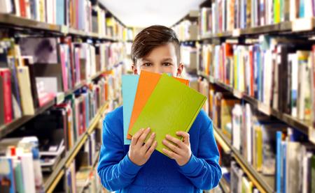 scuola, educazione e concetto di persone - ragazzo studente timido che si nasconde dietro i libri sugli scaffali sullo sfondo della biblioteca