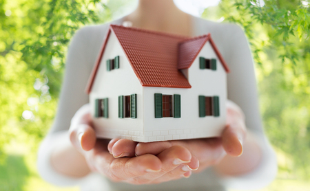 real estate, accommodation and property concept - close up of hands holding house or home model over green natural background