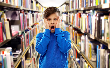 childhood, expressions and people concept - shocked or scared boy touching his face over book shelves at library background