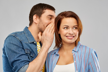 happy couple whispering over grey background