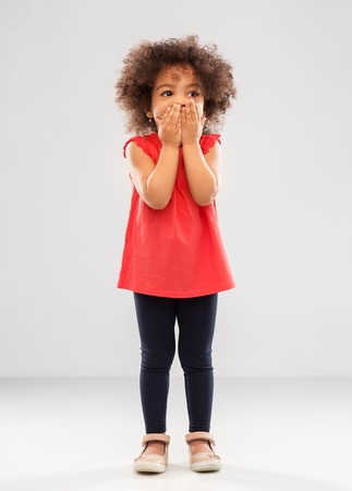 childhood, expression and emotion concept - confused little african american girl covering mouth by hands over grey background Stock Photo
