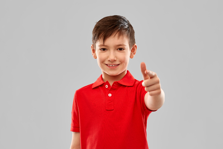 childhood, gesture and people concept - portrait of smiling little boy in red polo t-shirt pointing finger to you over grey background