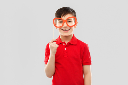 party props, photo booth and childhood concept - smiling little boy in red polo t-shirt with big paper glasses over grey background Stock fotó