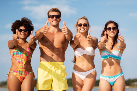 friendship, summer holidays and gesture concept - happy friends on beach showing thumbs up Foto de archivo