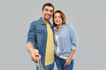 people concept - happy couple hugging and taking picture by selfie stick over grey background