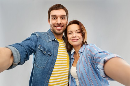people concept - happy couple hugging and taking selfie over grey background Stock Photo