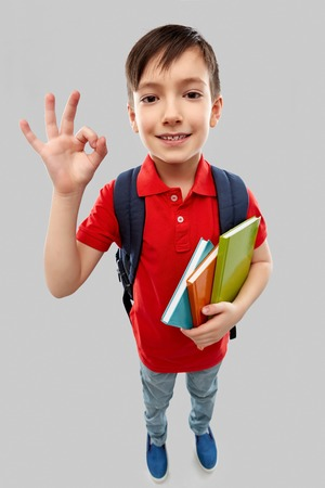 school, education and people concept - smiling little student boy in red polo t-shirt in glasses with books and bag showing ok hand sign over grey background Stock fotó