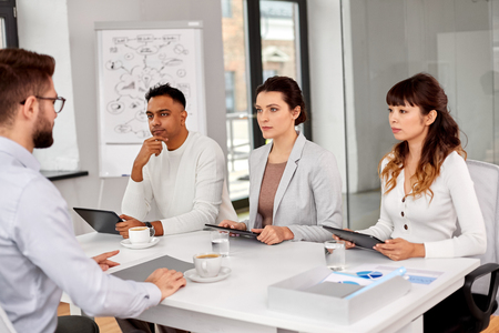 new job, hiring and employment concept - international team of recruiters with tablet pc computers having interview with male employee at office Stock Photo - 122218945