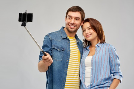 technology and people concept - happy couple hugging and taking picture by smartphone and selfie stick over grey background
