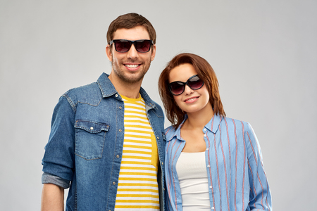 summer, eyewear and people concept - happy couple in sunglasses over grey background Фото со стока