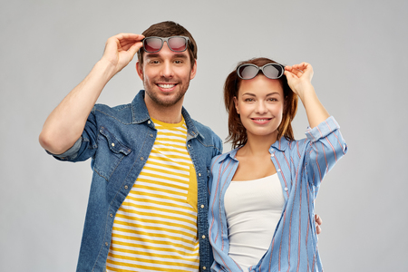 summer, eyewear and people concept - happy couple in sunglasses over grey background Imagens