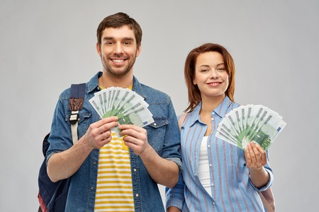 travel, tourism and vacation concept - happy couple of tourists with backpacks and money over grey background