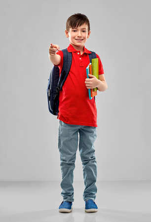 student boy with books and bag pointing to you