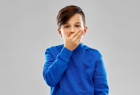 Childhood, expressions and people concept - shocked little boy in blue hoodie closing his mouth by hand over grey background